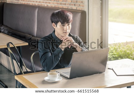 Young thoughtful businessman sitting with his laptop computer at a coffee shop, outdoors.