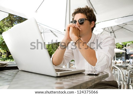 Young thoughtful businessman sitting with his laptop computer at a coffee shop terrace, outdoors. - stock photo
