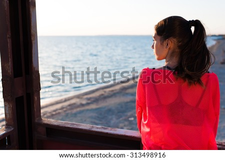 Young thoughtful charming woman enjoying beautiful landscape  in summer day while standing against blue sky and calm sea background with copy space area for your text message or advertising content - stock photo