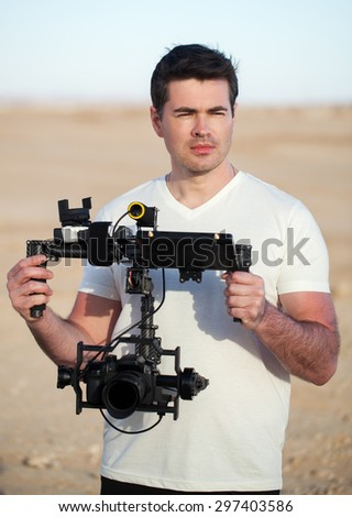 Young thoughtful man looking into distance while holding steadycam equipment in hands. Thinking over a video clip - stock photo