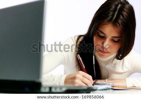 Young thoughtful student doing her homework - stock photo