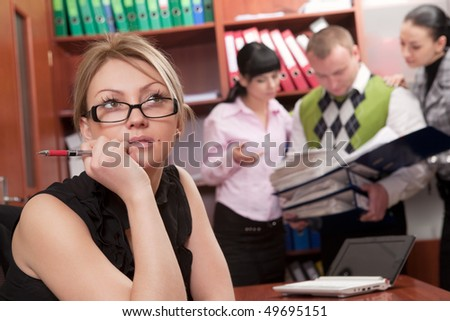 Young thoughtful woman at workplace with coworkers on background - stock photo
