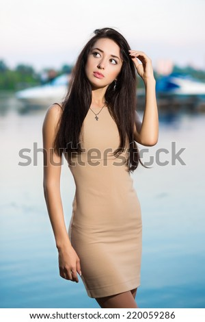 Young thoughtful woman in beige dress posing outdoors - stock photo