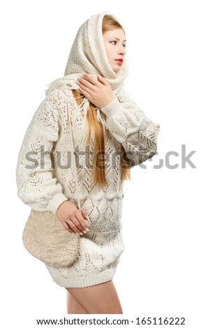 Young thoughtful woman in warm winter clothing with knitted bag walking isolated on white background - stock photo
