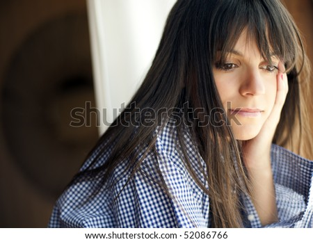 Young thoughtful woman looking outside - stock photo
