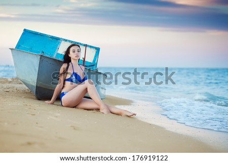 Young thoughtful woman posing near the boat