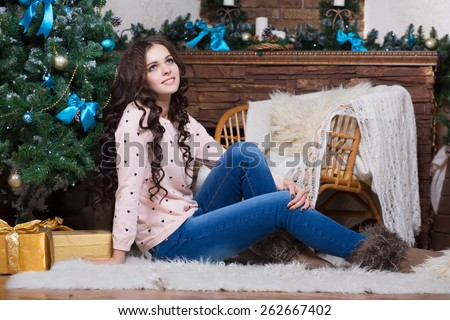 Young thoughtful woman sitting on the carpet near christmas tree and fireplace - stock photo