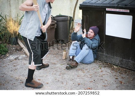 Young thug male threatening to beat a homeless man with a baseball bat.   - stock photo