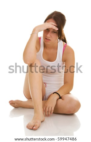 young tired and exhausted female in fitness outfit lies on white floor, studio shoot isolated on white