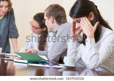 Young tired business woman with headache sitting at seminar - stock photo