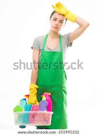 young tired caucasian woman holding cleaning supplies, on white background - stock photo