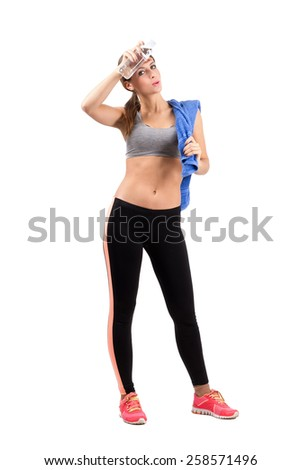 Young tired fitness woman wiping sweat from forehead with cool water bottle. Full body length portrait isolated over white background. - stock photo