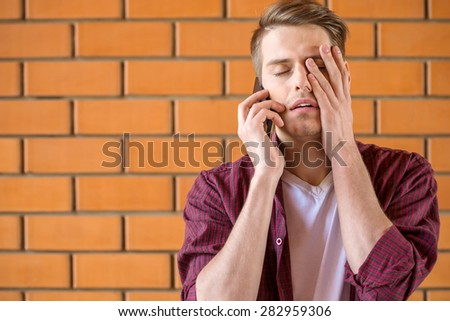 Young tired man talking on phone on brick wall background. - stock photo