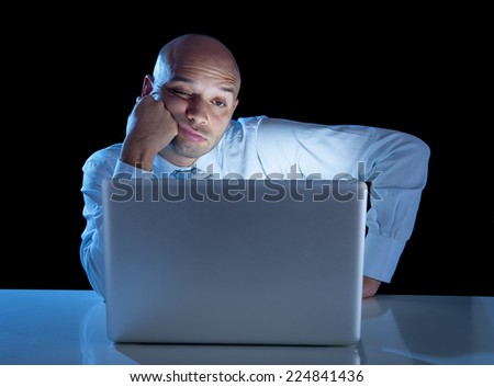 young tired overworked businessman working on computer laptop late night  exhausted and bored doing extra hours at work isolated on black background on project deadline concept - stock photo