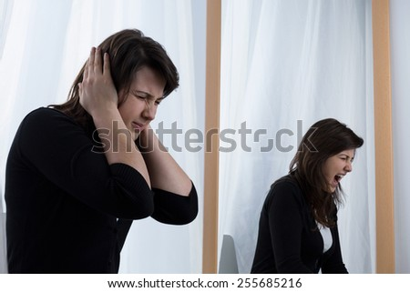 Young tired woman and her scramming reflection in the mirror - stock photo