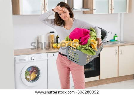 Young Tired Woman Carrying Basket With Clothes In Kitchen Room