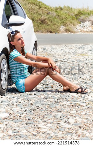 Young tired woman is sitting on the road near the car - stock photo