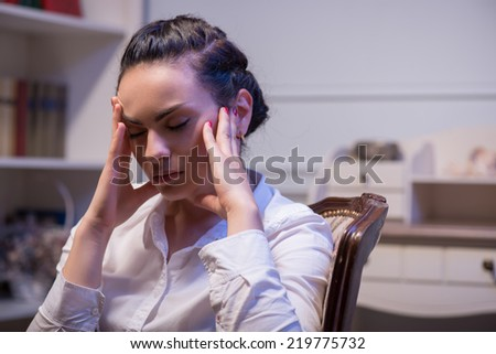 young tired woman wearing white blouse sitting in the chair with closed eyes holding at her head and thinking hard about big problems in her company. Her - stock photo