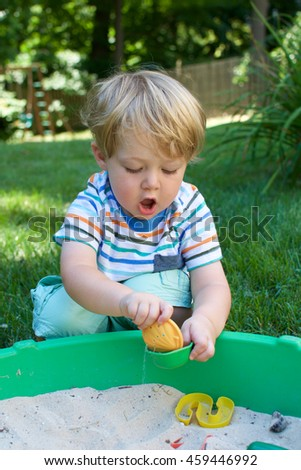 young toddler boy playing in sandbox