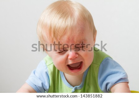 Young toddler crying away. Has his eyes closed and a huge open mouth from being so sad - stock photo