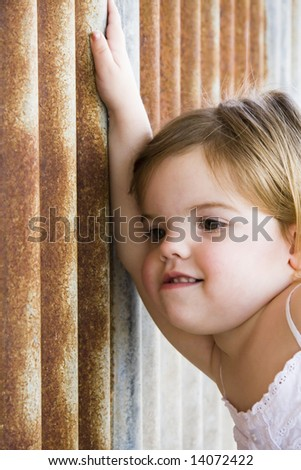 young toddler resting on an old rusty shed