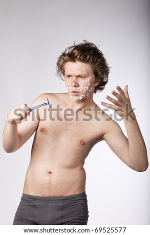 Young topless sexy man had bad luck while he was shaving with a razor. See more in my portfolio. - stock photo