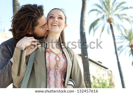 Young tourist attractive couple hugging and kissing while visiting a destination city on vacation during a sunny day.