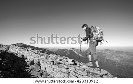 Young tourist backpacker walking on the rocky ridge of the mountain with beautiful high altitude landscape view on the background. Hiker using trekking sticks. black and white - stock photo