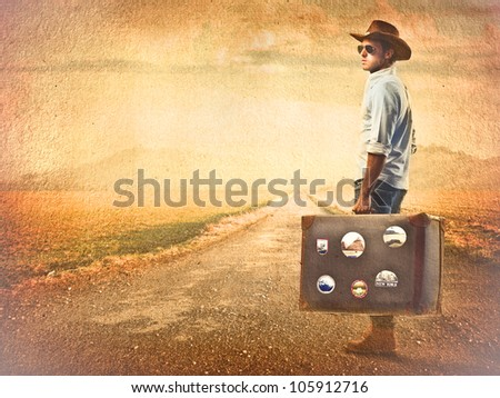 Young tourist carrying a suitcase on a country road at sunset - stock photo