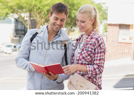 Young tourist couple consulting the guide book on a sunny day in the city - stock photo