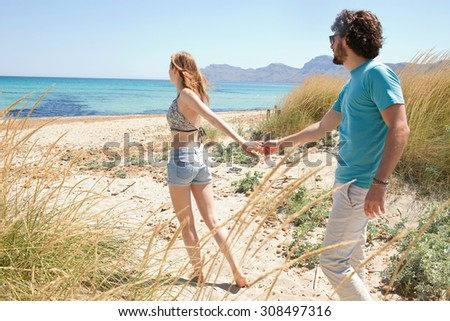 Young tourist couple having fun, woman taking man by the hand and pulling towards the sea, enjoying a summer holiday together on a beach exterior. Travel and lifestyle vacation, nature exterior. - stock photo