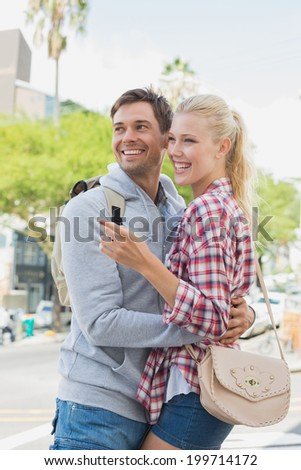 Young tourist couple pointing and looking on a sunny day in the city - stock photo
