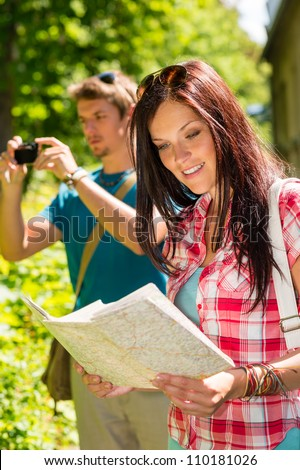 Young tourist couple travel holiday with map and photographing camera - stock photo