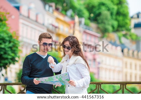 Young tourist couple traveling on holidays in Europe smiling happy. Caucasian family with city map in search of attractions - stock photo
