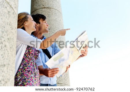 young tourist couple use their map to determine direction and point in the way they wish to go