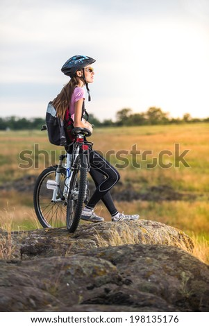Young tourist cyclist with backpack relaxing on rock and enjoying sunset - stock photo