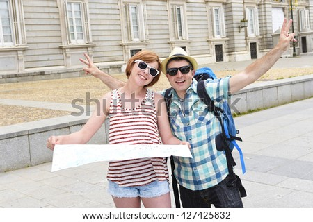 young tourist friends couple visiting Madrid in Spain together smiling happy and relaxed with man carrying travel backpack and girl holding the map enjoying holiday trip having fun - stock photo