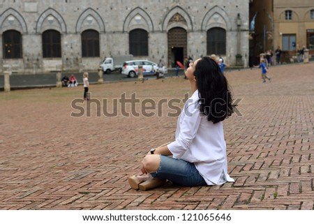 Young tourist girl sits on the medieval square of Siena. Italy - stock photo