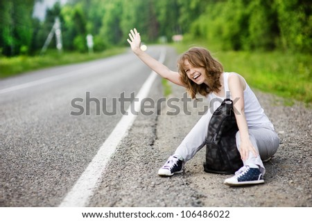 young  tourist hitchhiking along a road. - stock photo