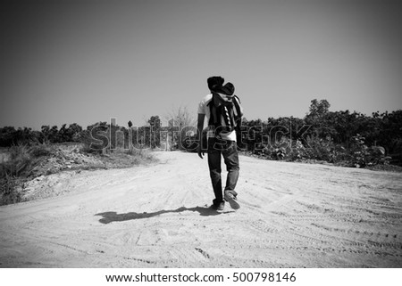 Young tourist man walking on the road,Man hitchhiking,Man  travel,Journey,Alone,Black and white