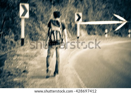 Young tourist man walking on the road,Man hitchhiking,Man  travel,Journey,Alone,Blurry portrait - stock photo