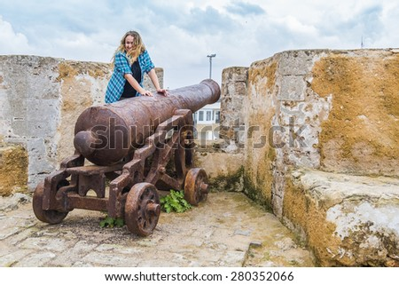 Young tourist posing on old cannon in El Jadida, Morocco - stock photo