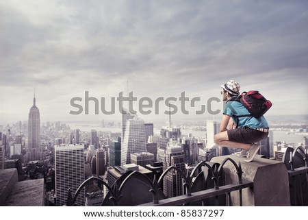 Young tourist sitting on the rooftop of a skyscraper over a big city - stock photo