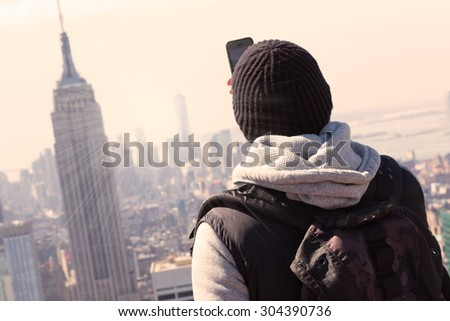Young tourist taking a photo of New York City panorama with his smart phone.. Manhattan downtown skyline with illuminated Empire State Building and skyscrapers at sunset seen from observation deck.  - stock photo