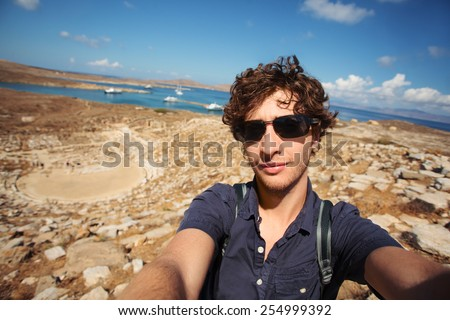Young tourist taking selfie with Amphitheater in Delos island in the background. Greece