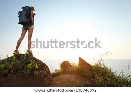 Young tourist with backpack standing on a rock and enjoying sunset