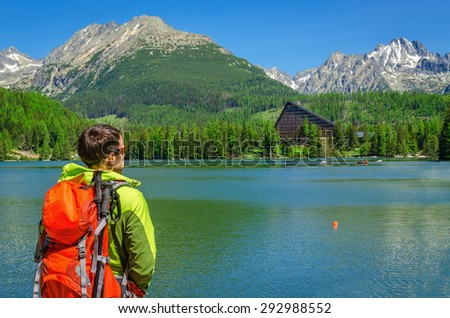 Young tourist with orange backpack on the back admiring the high peaks of the mountains and a beautiful lake