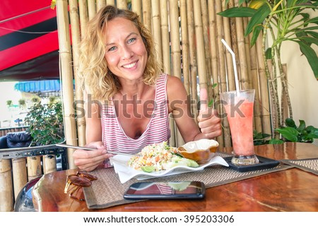 Young tourist woman eating fried rice and drinking fruit smoothie at thai restaurant in Phuket Thailand - Gastronomy concept with happy person traveler tasting local asian food - Happy smiling girl - stock photo
