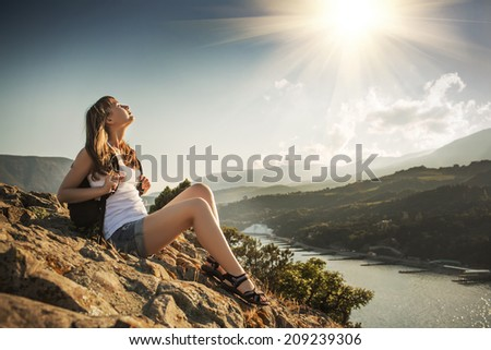 Young tourist woman is sitting on the top of the mounting and with pleasure looking at a beautiful sea landscape and sun