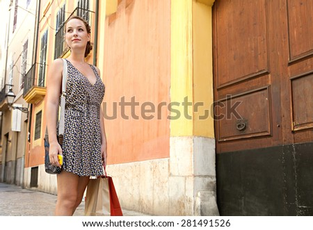Young tourist woman visiting a characterful destination city street, contemplating the architecture and carrying paper shopping bags on a summer holiday, outdoors. Travel lifestyle weekend break. - stock photo